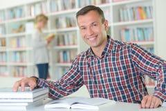 Lezer in de bibliotheek stock afbeeldingen