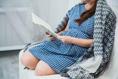 Lezing van de Unrecognisable de zwangere vrouw op bank onder grijze plaid stock afbeeldingen