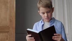Lezingsboek voor onderwijs van leuk kind of lerende schooljongen stock videobeelden