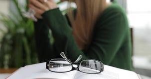 Lezingsconcept, oogglazenclose-up die, vrouw glazen nemen en boek lezen stock footage