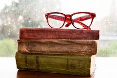 Lezingsglazen en boeken op regenachtig venster Royalty-vrije Stock Afbeelding