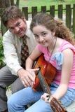 Lezione 3 della chitarra della figlia del padre Immagini Stock