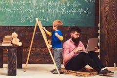 Lezione aritmetica alla scuola Scherzi la scrittura sulla lavagna mentre l'insegnante concentrato lavora al computer portatile Uo immagine stock