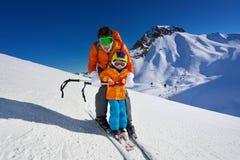 Lezione dello sci della montagna di elasticità del padre al ragazzino Fotografia Stock Libera da Diritti
