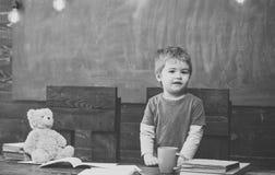 Lezione di arte all'asilo Bambino che sta dietro lo scrittorio di legno Tavola di legno scura con i quaderni, orsacchiotto, tazza Fotografia Stock