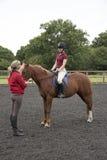 Lezione di guida con il cavaliere e l'istruttore Fotografia Stock