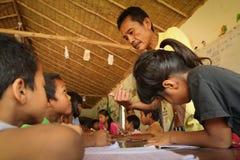 Lezione in un banco per i bambini del rifugiato Fotografia Stock