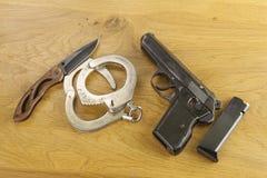 Lfirearm lying on the beach na stole, metal polici kajdanki Obrazy Royalty Free