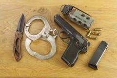 Lfirearm lying on the beach na stole, metal polici kajdanki Zdjęcie Stock