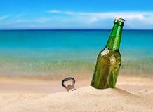 Ölflaska på en sandig strand Arkivbild
