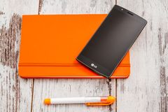 LG Smartphone, Orange Pen and Notebook royalty free stock photography