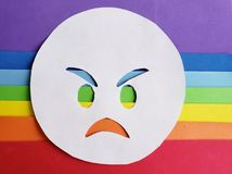 Angry emoticon on white and background with rainbow colors. Lgbt community, multicolor lines and stripes, expression and diversity royalty free stock photography