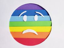 Sadness emoticon in rainbow colors and white background. Lgbt community, multicolor lines and stripes, expression and diversity stock photo