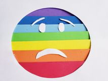 Sadness emoticon with rainbow colors and white background. Lgbt community, multicolor lines and stripes, expression and diversity royalty free stock photography