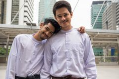 LGBT gay couple travel foreign country. Portrait of Handsome Myanmar gay couple with longyi traditional dress happy n in Modern Bangkok city. Smart guys smiling Royalty Free Stock Images