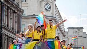 LGBT Gay Pride Parade, Man & Woman With Rainbow Flag On Open Top Bus. Stock Image