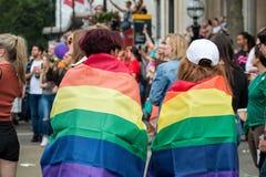 LGBT homosexuelles Pride Parade Two Young Woman eingewickelt in den Regenbogen-Flaggen Stockfotos