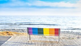 Seat in front of the beach painted with the colors of the LGBT flag. LGBT icon bench in front of the beach painted with the colors of the LGBT flag stock images