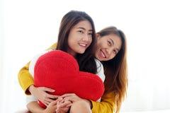 LGBT, lesbianas lindas jovenes de Asia huging y que llevan a cabo el shap rojo del corazón Fotografía de archivo
