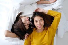 LGBT, lesbianas lindas jovenes de Asia que mienten y que sonríen en la cama blanca a Foto de archivo libre de regalías