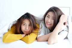 LGBT, lesbianas lindas jovenes de Asia que mienten y que sonríen en la cama blanca a Fotografía de archivo