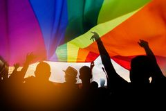 LGBT. Pride community at a parade with hands raised and the LGBT flag royalty free stock photography