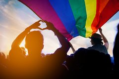 LGBT. Pride community at a parade with hands raised and the LGBT flag stock photos