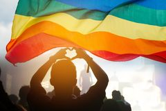 LGBT. Pride community at a parade with hands raised and the LGBT flag stock photography
