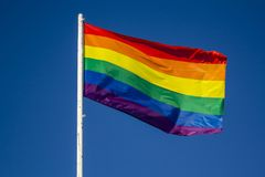 LGBT rainbow pride flag against blue sky. Background stock photography