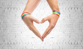 Male hands with gay pride wristbands showing heart. Lgbt, same-sex love and homosexual relationships concept - close up of male couple hands with gay pride stock image