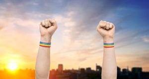 Hands with gay pride rainbow wristbands shows fist royalty free stock photography