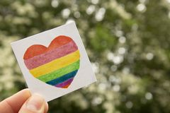 LGBT symbol. Hand holding watercolor rainbow heart. stock photo