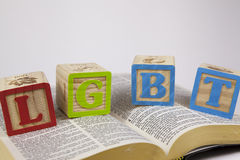 LGBT toy blocks on a bible. Childs toy blocks with LGBT sitting on a bible on white background Royalty Free Stock Photography