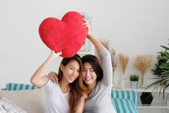 LGBT, Young cute asia lesbians holding red heart shape willow to. Gether smiling with happiness at home, couple lesbians, valentine`s day concept Stock Image