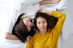 LGBT, Young cute asia lesbians lying and smiling on white bed to. Gether in the morning, couple lesbians happy moment Royalty Free Stock Photo