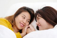 LGBT, Young cute asia lesbians lying and smiling on white bed to royalty free stock photos