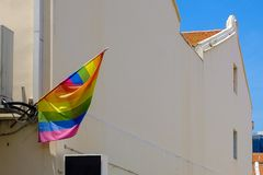 LGBTQ flag flying from a house for Lesbian, Gay, Bisexual, Transgender and Queer community.  royalty free stock photo