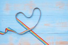 LGBTQ with heart shape Rainbow ribbon on blue pastel wooden background for Lesbian, Gay, Bisexual, Transgender and Queer community.  royalty free stock photography