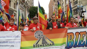 LGBTQ Immigrants March. Protesters and immigrants with rainbow flags and banners march for gay pride in downtown Los Angeles, California on May 1st, 2012 stock footage