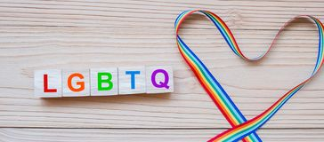 LGBTQ text with heart shape Rainbow ribbon for Lesbian, Gay, Bisexual, Transgender and Queer community.  royalty free stock photos
