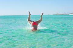 Lägger benen på ryggen den unga kvinnan för rolig undervattens- handstans upp Arkivbilder