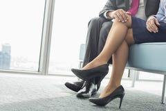 Lågt avsnitt av affärsmannen som i regeringsställning flörtar med den kvinnliga kollegan Arkivbild