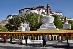 LHASA, TYBET region autonomiczny, CHINY - OKOŁO MAJ 2018: Ludzie chodzi wzdłuż tibetan modlitewnych kół z trzy białymi stupas w obrazy stock