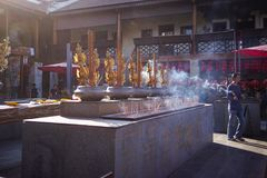 Lhong 1919, a man bring burning incense for praying. Lhong 1919 was built by Phraya Phisasuppapol, the ancestor of the Bisalputra family. Originally called Huo Stock Images
