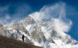 Lhotse with windstorm, turist and snow clouds. Top of Lhotse and Nuptse with windstorm, turist and snow clouds on the top Royalty Free Stock Photos