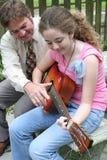 Lição 1 da guitarra da filha do pai foto de stock