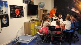 Lição exterior do ` s das crianças para o estudo do cosmos com o professor na sala de aula filme