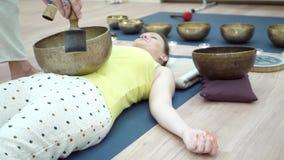 Lição praticando da ioga da mulher desportiva nova com o instrutor no gym filme