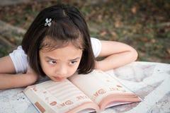 Lições aborrecidas da criança asiática pequena que leem um livro imagem de stock