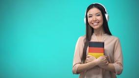 Lições audio alemãs de escuta da menina nos auriculares, livro nas mãos, traduções vídeos de arquivo